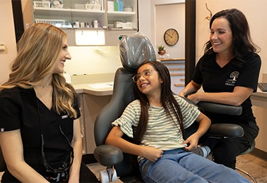 Team member talking to smiling patient in dental chair