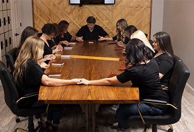 Team members in conference room praying together