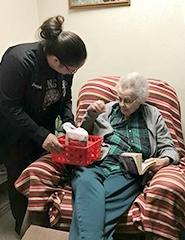 Team member giving gift to senior citizen at community event