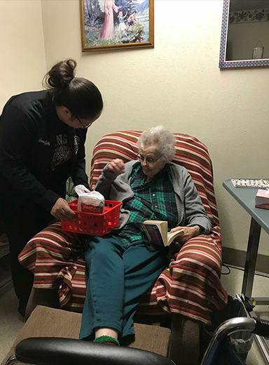 Team member giving older patient a gift