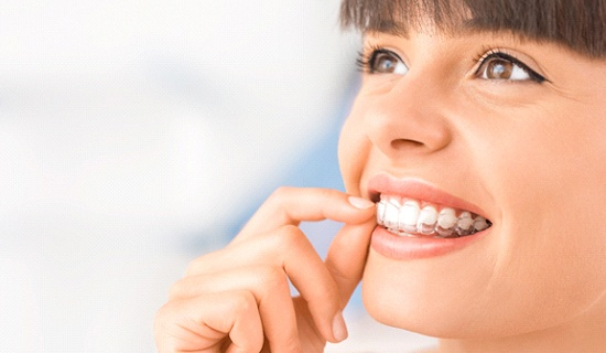 Woman smiling while putting Invisalign trays in