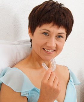 A woman holding an oral appliance before going to bed