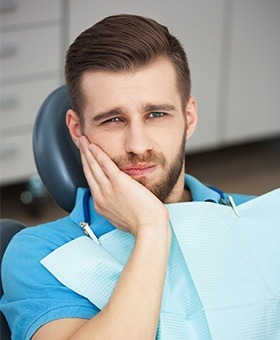 Man in dental chair holding his jaw