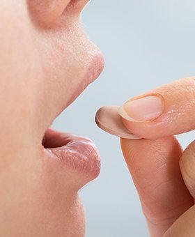 Closeup of person taking oral conscious sedative pill