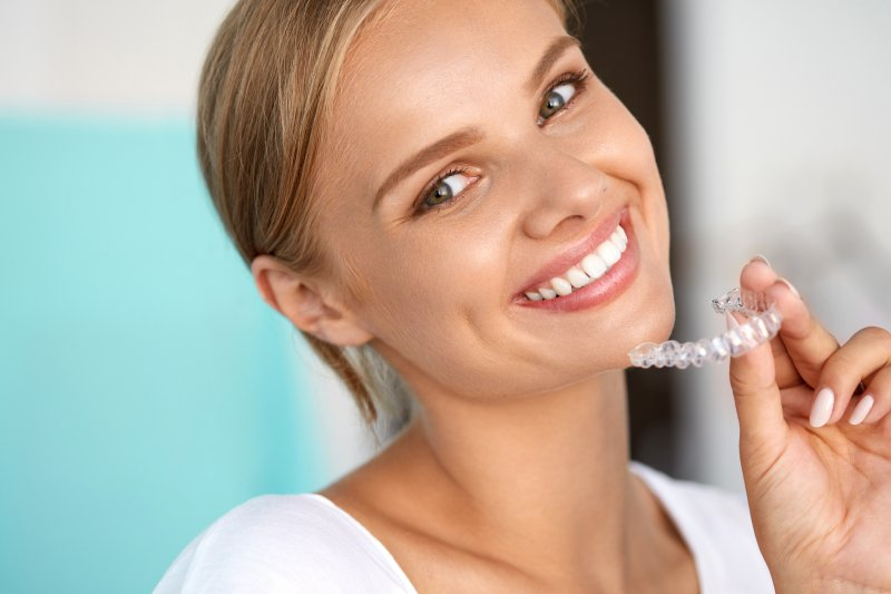 Woman holding clear aligner for Invisalign after braces